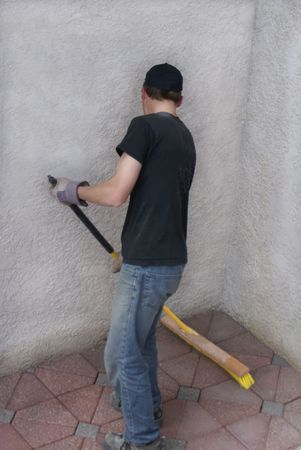 Construction worker sweeping up tiles with broom