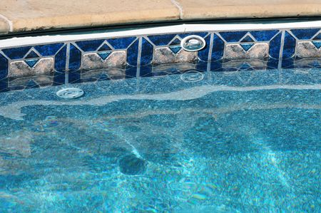 edge: Turquois blue water swirling at edge of swimming pool with mosaic edge Stock Photo