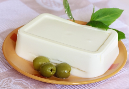 Olives, cream cheese and basil on the orange plate
