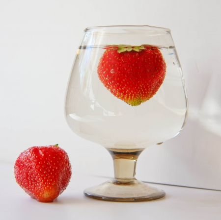 Strawberries in a glass of water on a light background Stock Photo - 14190371