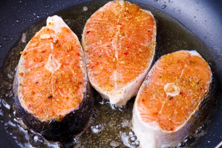 Frying fresh salmon on the pan photo