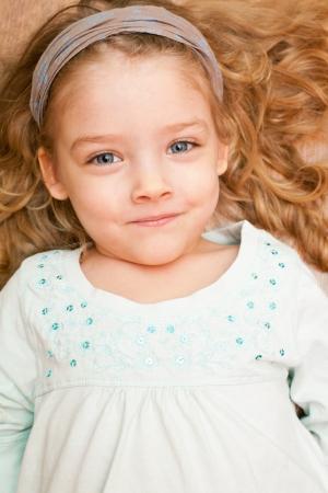 lies down: Happy little girl lying on floor