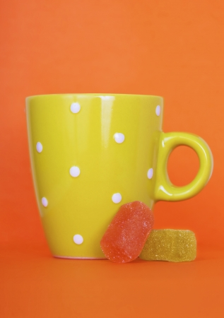 Green cup and marmalade on orange background photo