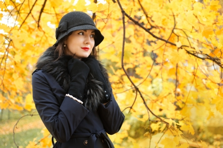 Woman in a black hat on a background of yellow autumn tree