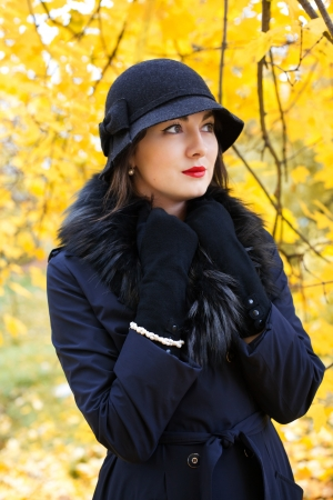 understated: Woman in a black hat on a background of yellow autumn tree