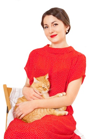 Beautiful woman in a red dress with a cat in her arms Stock Photo - 23948677