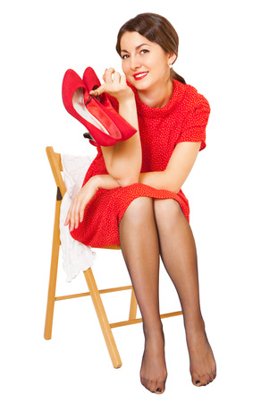 Beautiful woman with red shoes in hand, isolated on white photo