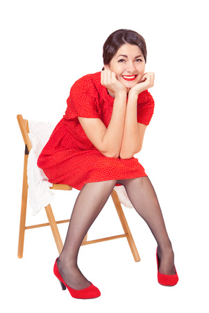 Happy woman in red dress sitting on a chair, isolated on white background photo