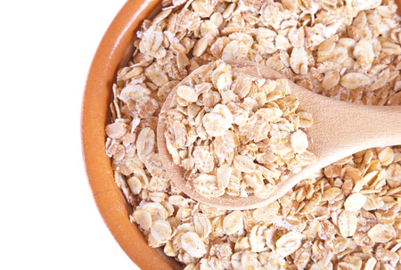 The oat flakes on a wooden spoon and plate photo