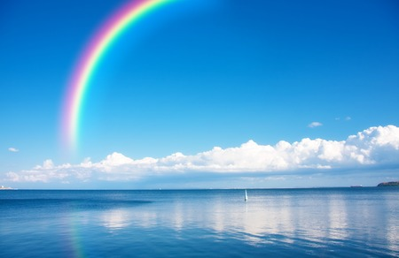 A rainbow on blue sky over endless water Stock Photo - 27478268