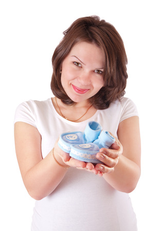 Portrait of pregnant woman with baby shoes, isolated photo