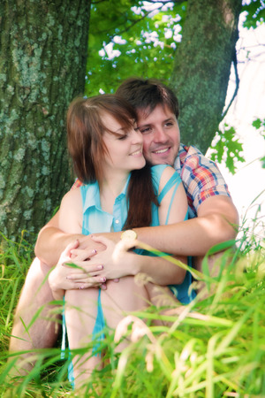 Smiling couple resting near a tree photo