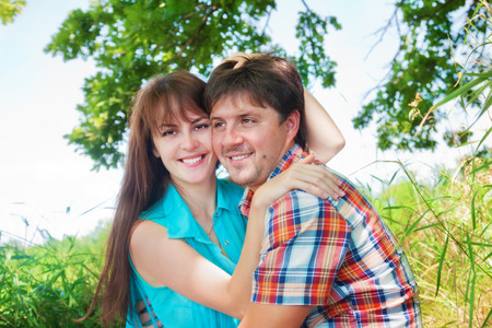 Smiling couple resting near a tree Stock Photo
