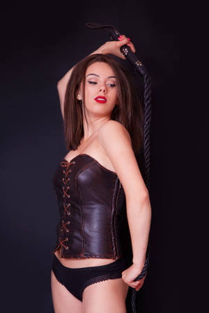 female domination: Woman with a whip in her hand