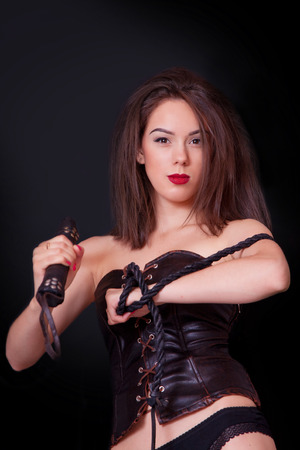 Woman on a black background with a whip in her hand photo