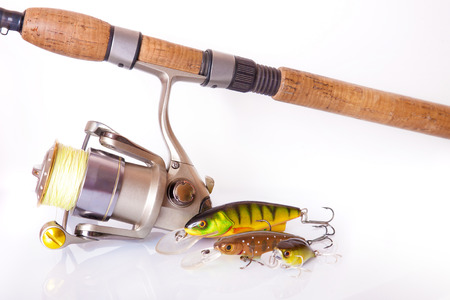 Spinning rod and reel with wobbler lure on white background