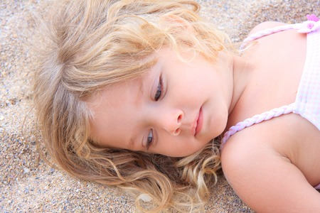 dreamy eyed: Little girl lying on the sand, on the beach