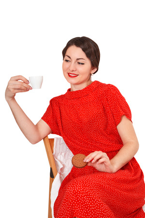 Pretty woman holding a cup of coffee and cookies photo