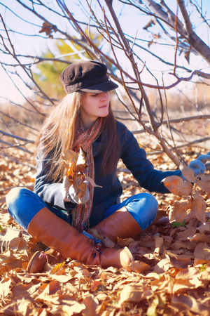 Girl with pensive look sitting near a tree with dry leaves in hand photo