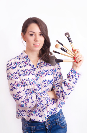 Girl makeup artist with brushes in hand