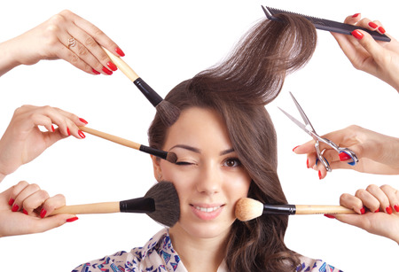 Girl and a lot of hands with comb, scissors and brushes for makeup