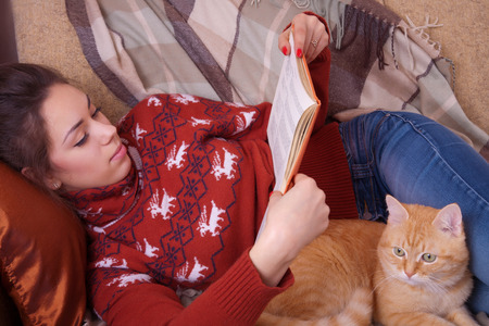 Cute girl lying on the sofa with red cat and reading a book