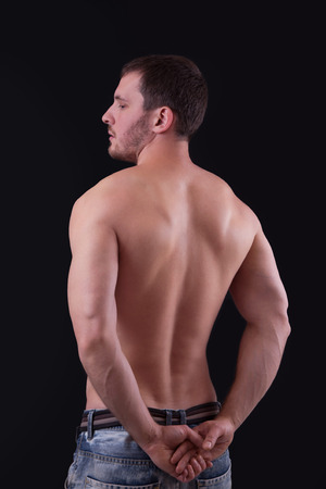 barechested: Rear view of a well-built bare-chested young man