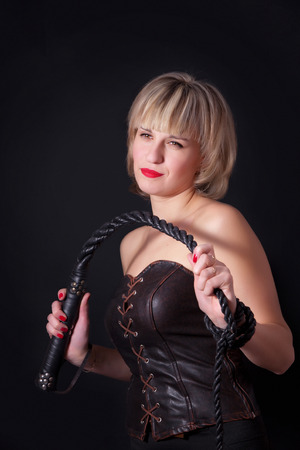 Woman on a black background with a whip in her hand Stock Photo