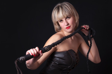 domination: Woman on a black background with a whip in her hand Stock Photo