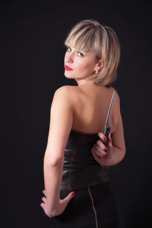 A blond model with large knife behind her back