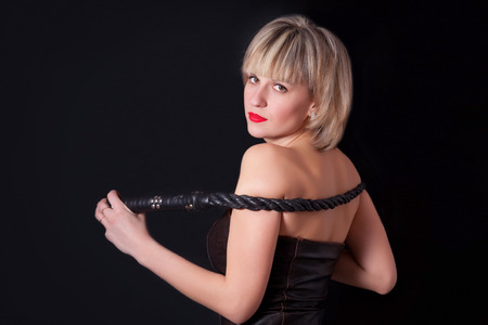 masochism: Woman on a black background with a whip in her hand Stock Photo