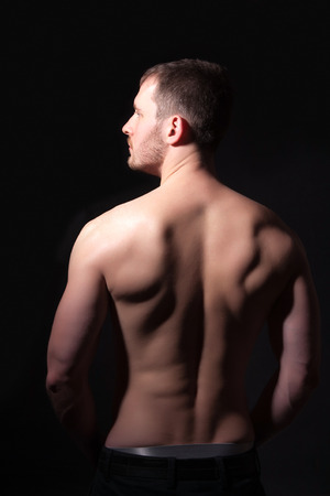 hands behind head: Rear view of a well-built bare-chested young man