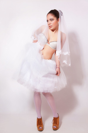 Bride in a skirt, underwear and veil on gray background Stock Photo