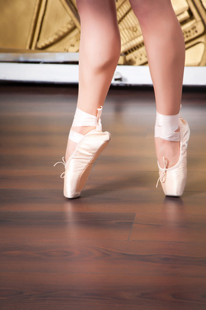 pointes: Ballerina legs in pointes in dancing hall, against the backdrop of the piano