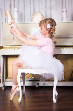 Ballerina in pointe shoes sitting on a chair near the piano