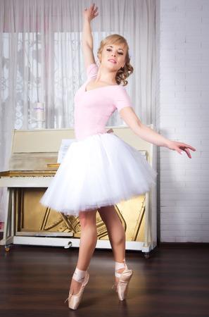 Young beautiful ballerina posing in dance studio Stock Photo