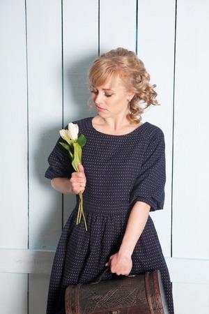 mujer con maleta: Mujer bonita con flores en la mano y una maleta
