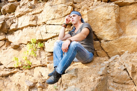 loner: Man resting in the mountains sitting on the rock