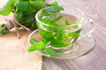 Cup of mint tea and a bunch of mint on the table Stok Fotoğraf - 46691308
