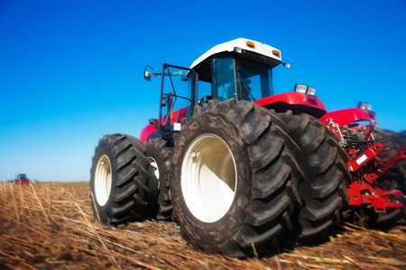 wheel tractor: Red tractor in the field on a sunny day Stock Photo