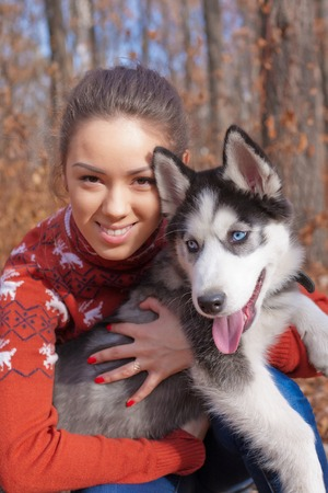 huskies: Beautiful young woman hugging huskies puppy for a walk in the park in autumn