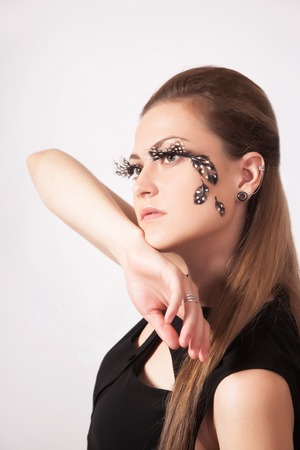 faceart: Beautiful woman with big eyelashes and face-art, studio shooting
