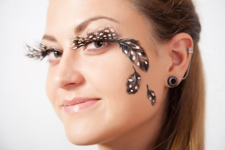 faceart: Beautiful woman with long eyelashes and face-art, close-up