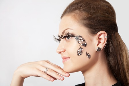 faceart: Beautiful woman with long eyelashes and face-art  in profile, close-up
