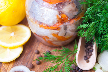 Marinated herring in a jar with vegetables and herbs