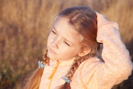 far away look: Portrait of a girl with pigtails closeup on a sunny day outdoors Stock Photo