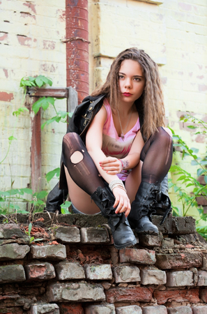 torn stockings: Portrait of a young woman in torn stockings and a leather jacket outdoors Stock Photo