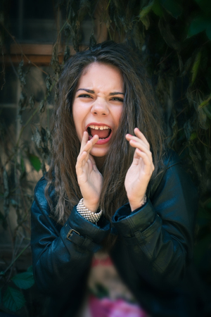 girl posing: Young woman screaming on a background of the old wall