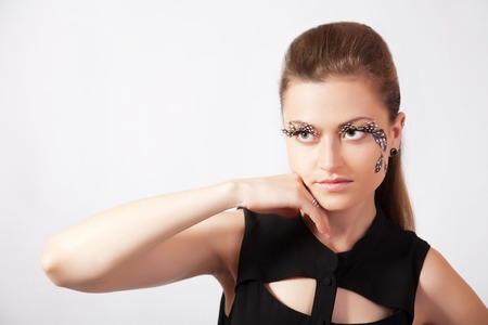 faceart: Beautiful woman with big eyelashes and face-art Stock Photo
