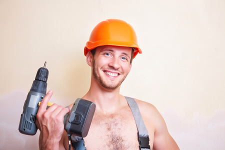only man: A man in overalls and helmet with a screwdriver